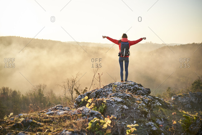 Woman on a hiking trip in the mountains standing on rock enjoying the view