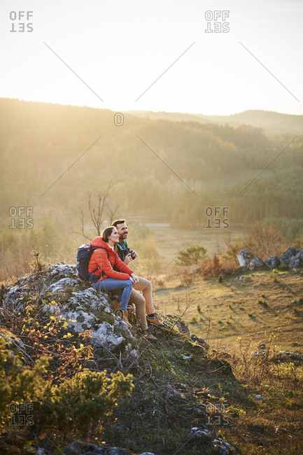 Couple on a hiking trip in the mountains having a break sitting on rock