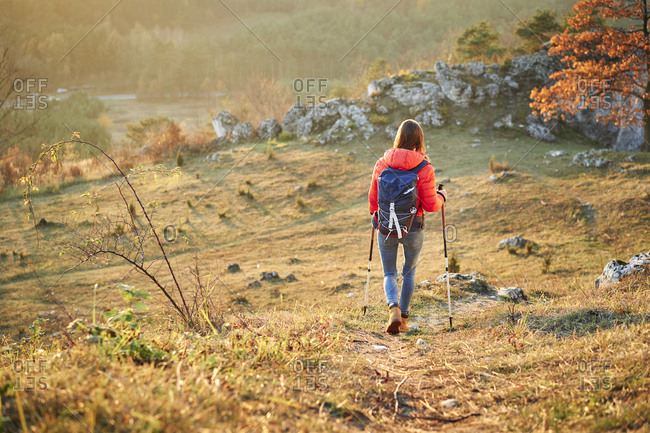 Rear view of woman walking on trail on a hiking trip in the mountains