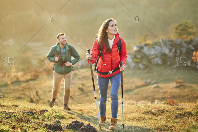 Couple walking on alpine meadow on a hiking trip in the mountains