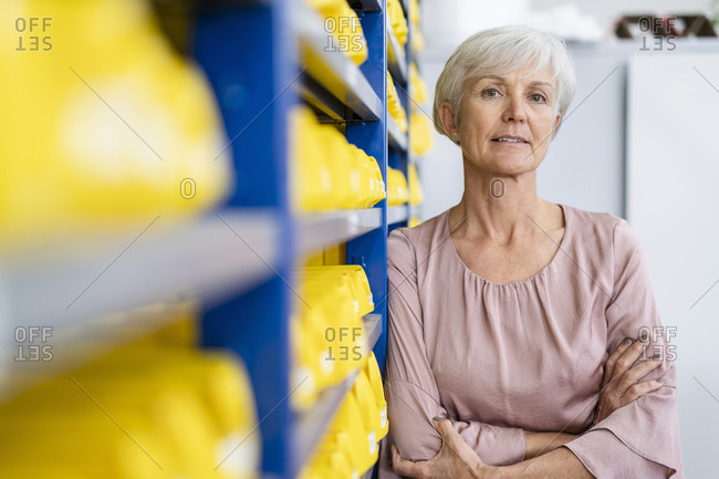 Portrait of confident senior woman in storehouse of a factory