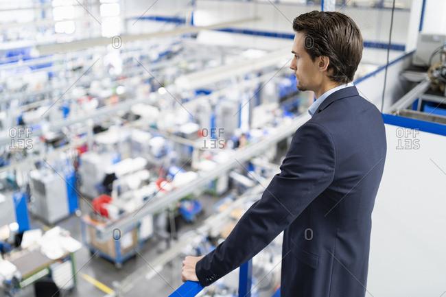 Businessman on upper floor in factory overlooking shop floor