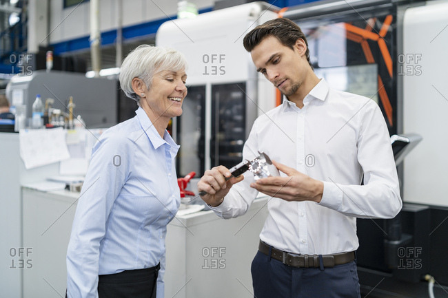 Businessman and senior businesswoman measuring work piece in a factory