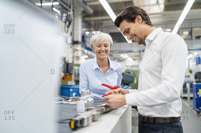 Happy businessman and senior businesswoman examining work piece in a factory