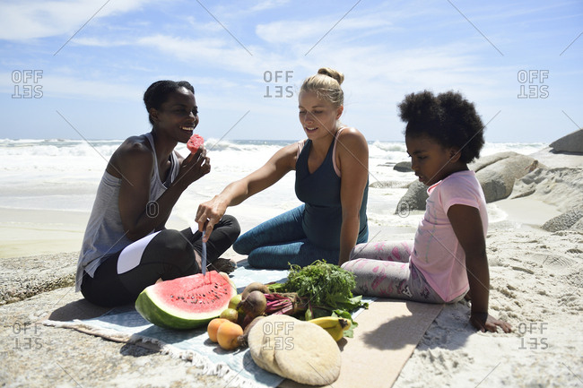 Mother with daughter and friend having a picnic on the beach