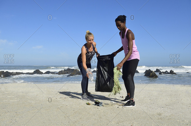Two women cleaning the beach from plastic waste