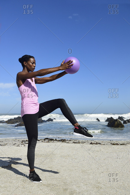 Woman doing fitness exercise with ball on the beach