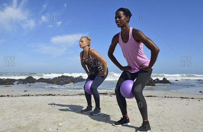 Two women doing fitness exercises with ball on the beach
