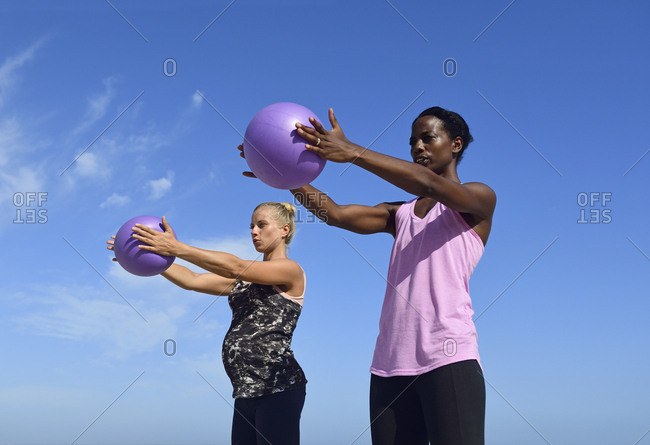 Two women doing fitness exercises with ball under blue sky