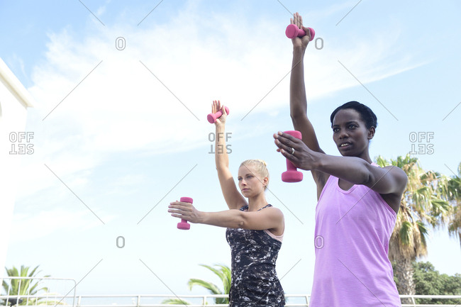 Two women doing fitness exercises with dumbbells outdoors