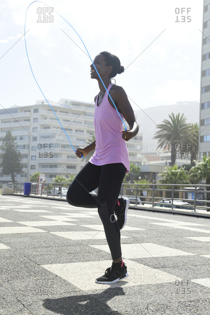 Sportive woman skipping rope outdoors