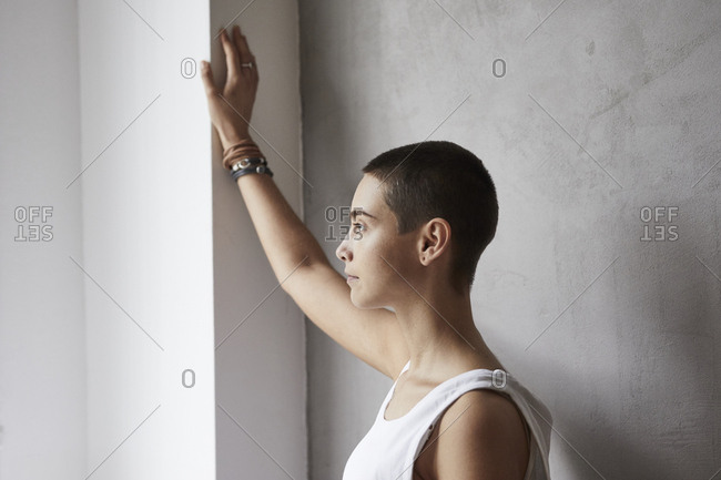 Short-haired young woman wearing vest looking out of window