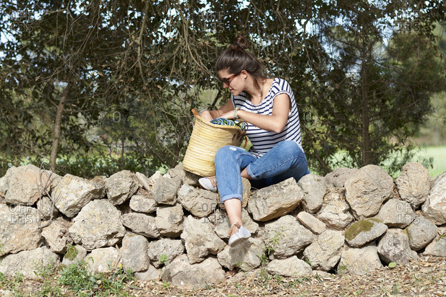 Spain- Menorca- young woman with bag sitting on stone wall