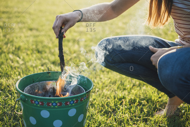 Woman barbecuing on a meadow- partial view