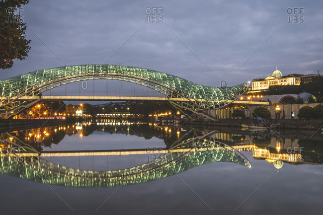 Georgia- Tbilisi- Bridge of Peace over river Kura at night with parliament in background