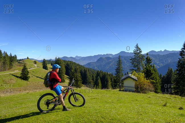 Germany- Mountain biker looking to Hirschtalsattel- Aueralm with Tegernsee Mountains near Lenggries