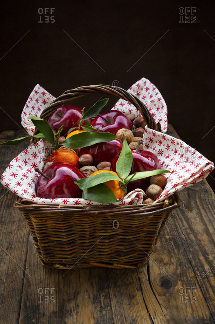 Wicker basket of red apples- tangerines- hazelnuts and walnuts