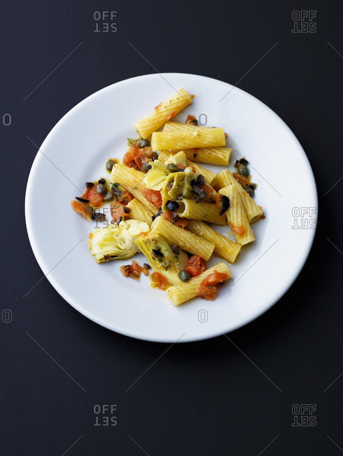 Plate of Tortiglioni with artichoke- olives- tomato and capers