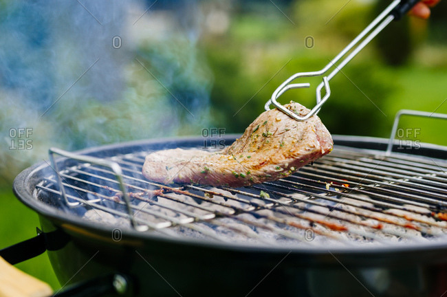 Grilling lamb fillet on charcoal grill