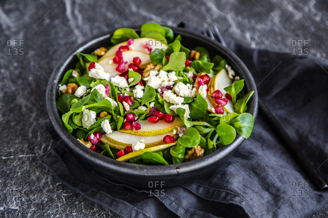 Bowl of mixed salad with lamb's lettuce- feta- pear- pomegranate seed and walnuts