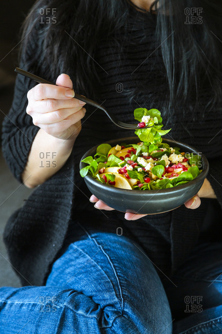 Woman eating mixed salad with lamb's lettuce- feta- pear- pomegranate seed and walnuts