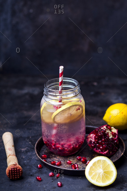 Fruit infused water with lemon slices- crushed pomegranate seeds and sparkling water
