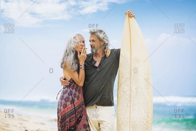 Senior hippie couple with surfboard on the beach