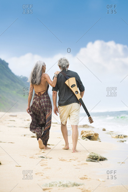 Back view of senior hippie couple with guitar strolling side by side on the beach