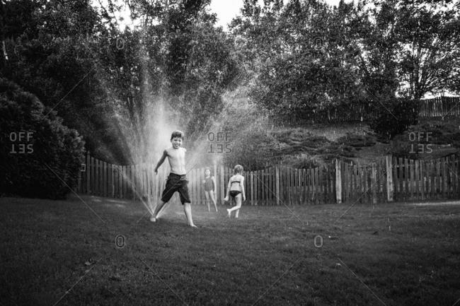Kids play around sprinklers