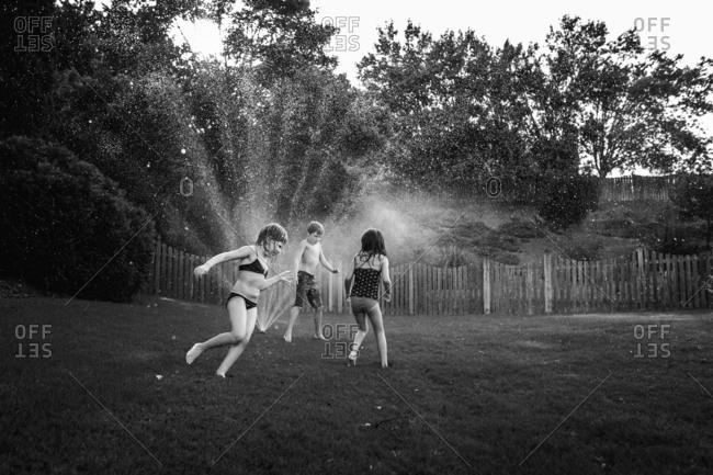 Kids run around sprinklers