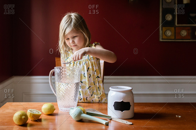 Young girl making lemonade at home in a glass pitcher