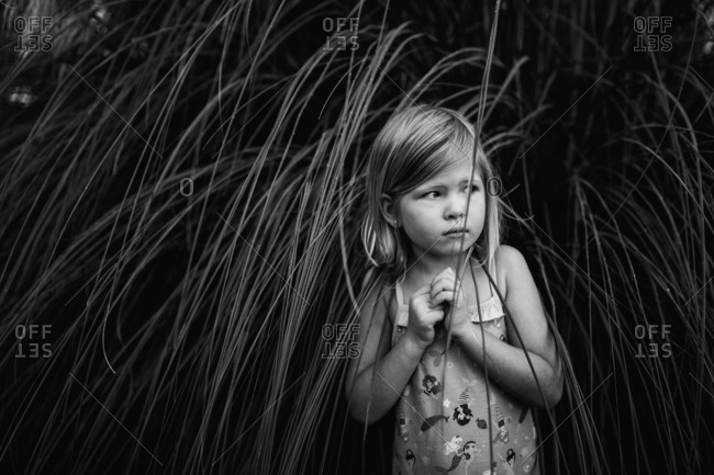 Young girl hiding in tall grass
