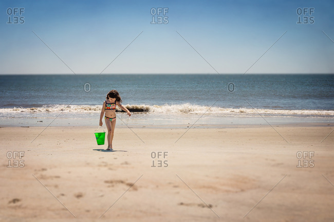 Girl carrying a bucket on the beach