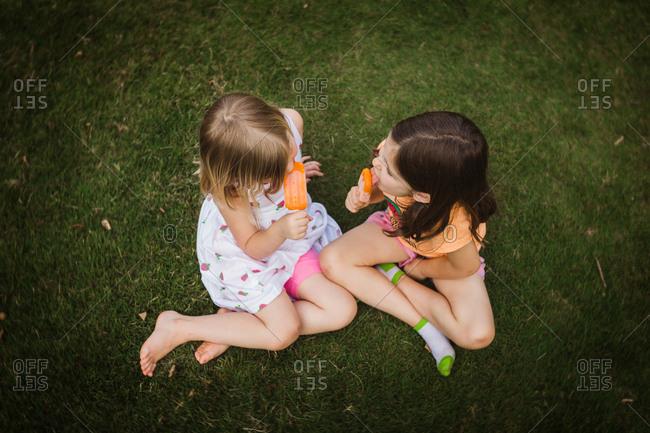Girls eat orange popsicles outside
