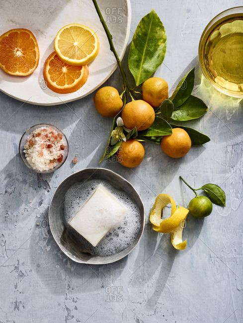 Homeopathic soap on a plate with lemon, lime and oranges near a dish of salt.