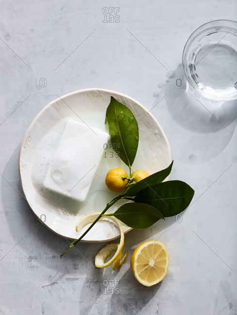 Homeopathic soap on a plate with lemon near a glass of water.