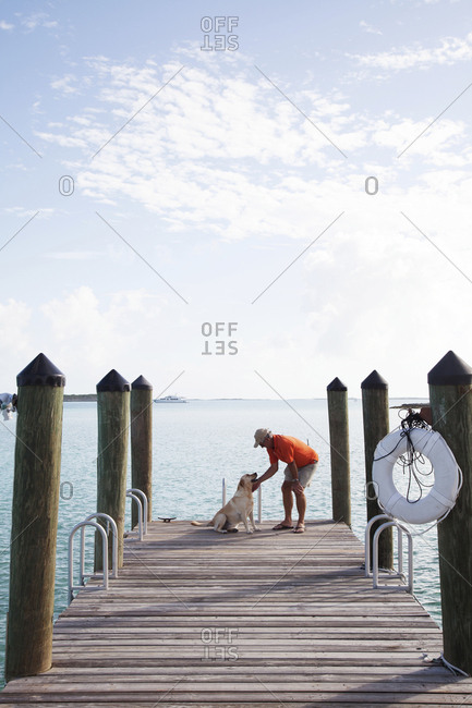 October 27, 2011: EXUMA, Bahamas. Yves and resident dog, Ruby, hanging out on the dock of the Fowl Cay Resort.