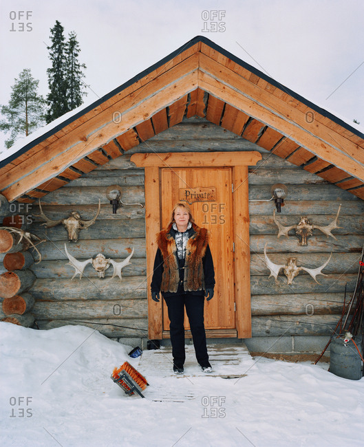 October 4, 2010: FINLAND, Artic, Nunnanen, Mature woman standing in front of husky farm