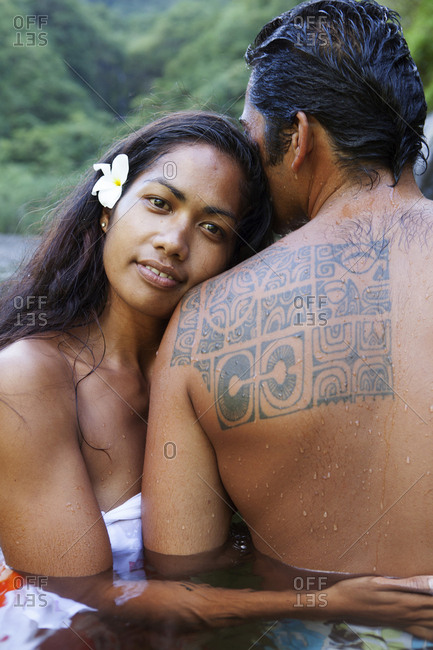 April 6, 2010: FRENCH POLYNESIA, Tahiti. A local swimming hole close to the town of Papenoo along a dirt road towards the center of the island. A local couple swimming in the water.
