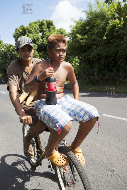 April 7, 2010: FRENCH POLYNESIA, Tahiti. A couple of boys on a bicycle with bread and bottle of coke in the village of Vairao located along the southern coastline of Tahiti Island.