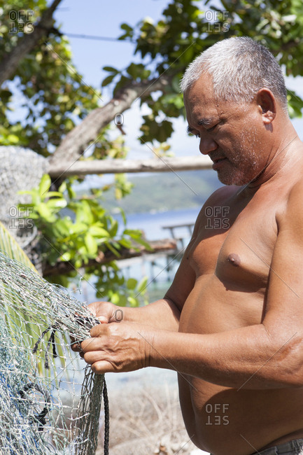 April 8, 2010: FRENCH POLYNESIA. Atger on his own island, Atger Island, standing and fixing his fishing nets.
