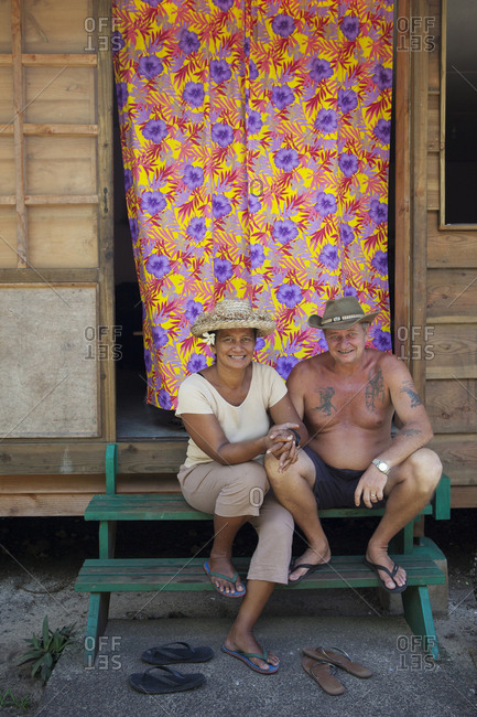 April 8, 2010: FRENCH POLYNESIA, Tahaa Island. Brian and Moeota Hansen sitting in front of their house at their Vanilla Farm.