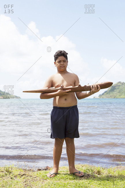 April 9, 2010: FRENCH POLYNESIA, Tahaa Island. Chris, a young boy holding a wooden canoe made by his father. His father is a sculpture and sells his pieces from their home.