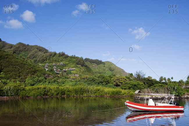 April 11, 2010: FRENCH POLYNESIA, Moorea Island. A boat anchored along the coastline with a view of the Legends Resort bungalows along the mountain in the background.