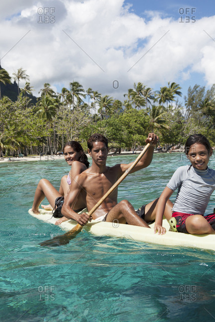 April 11, 2010: FRENCH POLYNESIA, Moorea. Young kids on canoe at Opunohu Bay.