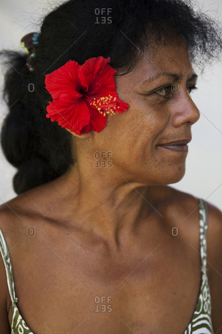 April 14, 2010: FRENCH POLYNESIA, Moorea. Portrait of woman with flower at the Te Nunoa Private Garden Bungalow.