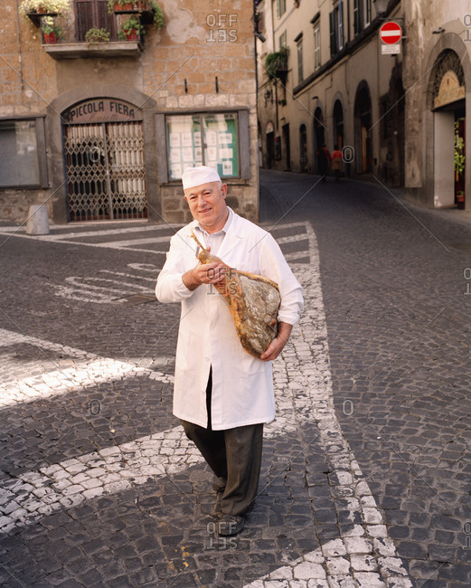 February 16, 2010: ITALY, Orvieto, Umbria, Butcher Adorno Mocetti carrying prosciutto while crossing the street.