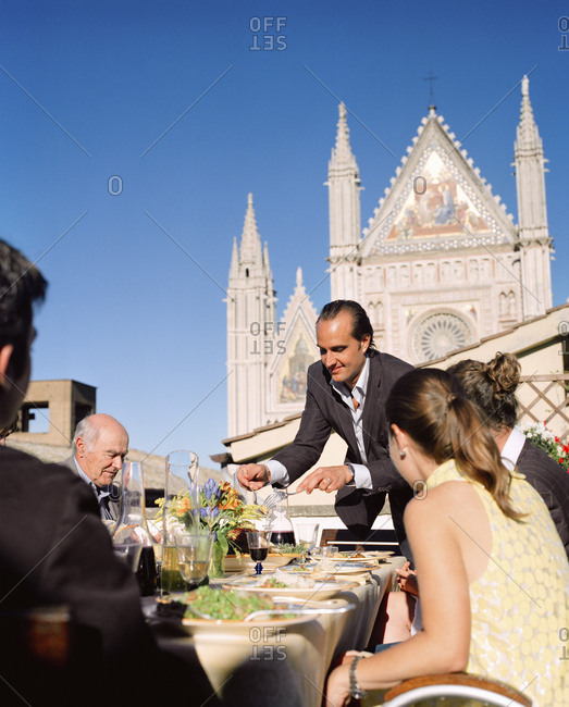 February 16, 2010: ITALY, Orvieto, Umbria, Chef Alex Palermo serving lunch on the rooftop of his family home with the Orvieto Cathedral in the background.