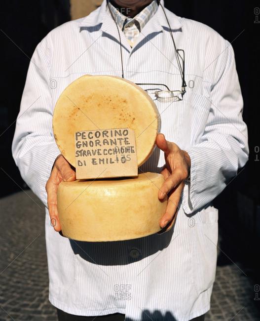 February 16, 2010: ITALY, Orvieto, Umbria, butcher Emilio Batalocco holding pecorino cheese.