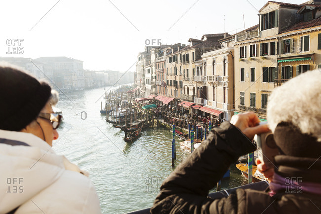 December 30, 2010: ITALY, Venice. Tourists taking pictures of the Grand Canal from the Rialto Bridge.
